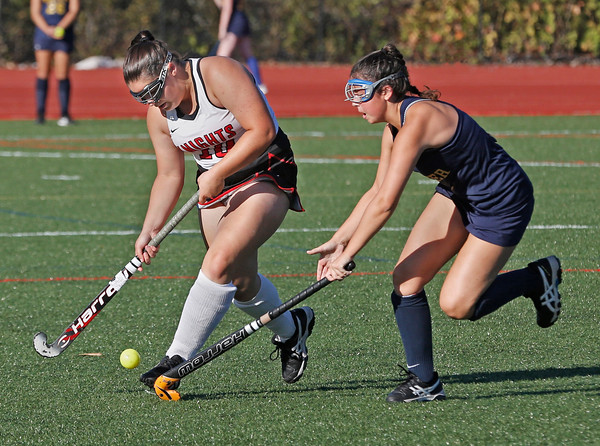 MIKE SPRINGER/Staff photo<br /> North Andover's Kiki Valentino, left, moves the ball upfield under defensive pressure from Heather Graham of Andover during varsity field hockey play Wednesday at North Andover.<br /> 9/25/2019