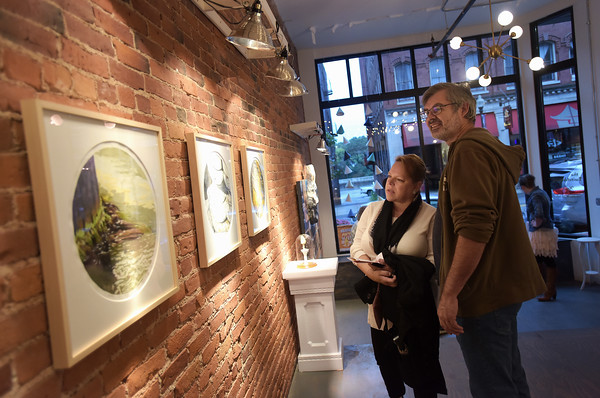 TIM JEAN/Staff photo<br /> <br /> Richard and Shirleen Woodward, of Bradford, look over works of art by Marc Mannheimer on exhibit in the Switchboard gallery during the first annual Art Walk throughout downtown Haverhill. The event featured local artists painting around the city streets, open studios, demonstrations and performances at a dozens businesses.    9/14/19
