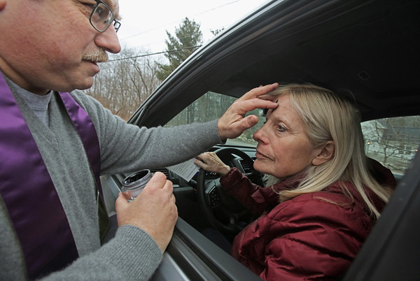 """MIKE SPRINGER/Staff photo<br /> Pam Guischard of Atkinson receives ashes on her forehead from Pastor Jim Thomas during an """"ashes to go"""" drive-up Ash Wednesday service Wednesday at the Atkinson Congregational Church in Atkinson, New Hampshire. Rev. Thomas held a traditional Ash Wednesday service inside the church later in the day, but provided ashes to motorists as a service to people on the go.<br /> 2/27/2020"""