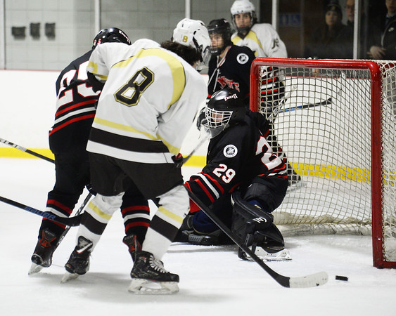CARL RUSSO/Staff photo Haverhill's Evan Foskett, 8 is unable to capitalize on the open corner as North Andover's Nick Herald ties him up after North Andover's goalie, Patrick Green makes the initial save. North Andover defeated Haverhill 6-2 in boys' hockey action. 2/05/2020