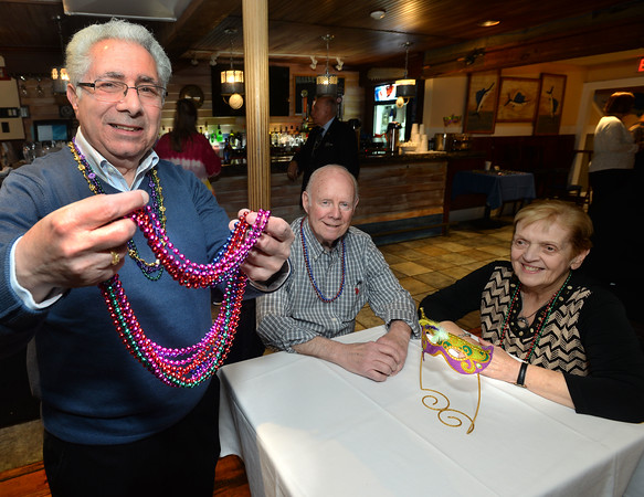 CARL RUSSO/Staff photo The Holy Name Society of Corpus Christi Parish at Holy Rosary Church celebrated its 60th. annual Mardi Gras Carnevale on Sunday afternoon, February 23, at Joe Fish Restaurant in North Andover.  <br /> <br /> President of the Holy Name Society, Carl Benanti of Methuen, left, offers some Mardi Gras beads to Gene and Eleanor Thornhill of Lawrence. <br /> <br /> Around 50-60 people enjoyed a buffet style dinner with dessert, raffle and socializing with new and old friends. The highlight of the day was the crowning of the Mardi Gras' king and queen. 2/23/2020