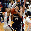 CARL RUSSO/Staff photo Lawrence's captain, Gabriel Zorrilla fights to make the lay up against Central's captain, Anthony Traficante, right and Marcus Rivera. Central Catholic played against Lawrence in boys basketball action Tuesday night. 2/11/2020