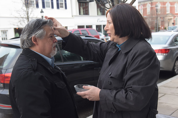TIM JEAN/Staff photo <br /> <br /> Renee Manning, right, from South Church blesses Steve Longo, of Andover, with ashes on Ash Wednesday outside of Starbucks in Andover. This year marked the fifth year South Church has given out ashes on the go in downtown Andover. 2/26/20