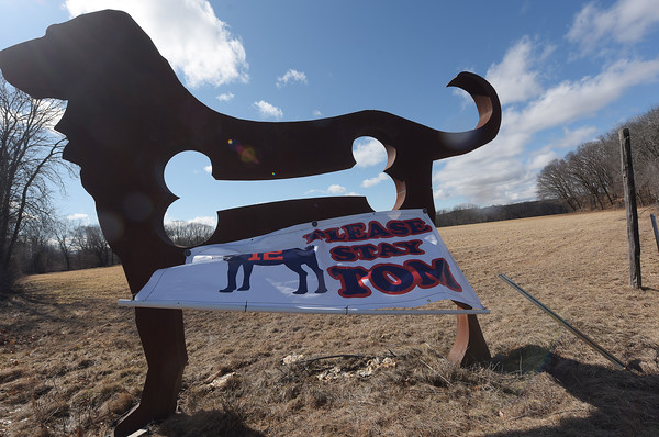 TIM JEAN/Staff photo <br /> <br /> Metal sculptor Dale Rogers, of Haverhill, has hung a banner one of his 16-foot tall American Dog sculpture on Route 495 South at the exit 48 off ramp that reads Please Stay Tom.   2/27/20