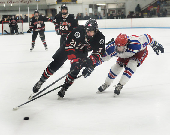 CARL RUSSO/Staff photo North Andover's Andrew Perry fights for the puck with Tewksbury's Tom Barbati. Perry scored the second goal for the Knights. <br /> <br /> North Andover defeated Tewksbury 3-2 in Div. 2 hockey quarterfinals at the Chelmsford Forum Friday night. 2/28/2020