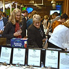 RYAN HUTTON/ Staff photo<br /> Jeanne Osborn, right, looks over some of the auction items up for bod at the GLOW Gala at Everett Mill in Lawrence on Thursday night, November 14 marking the 20th anniversary of Groundwork Lawrence. 11/14/2019