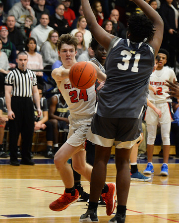 CARL RUSSO/Staff photo. Central's captain, Nate Godin passes the ball to his teammate under the basket as Haverhill's Jeremy Valdez defends. Central Catholic defeated Haverhill in boys basketball in D1 North opener Monday night.  2/24/2020.