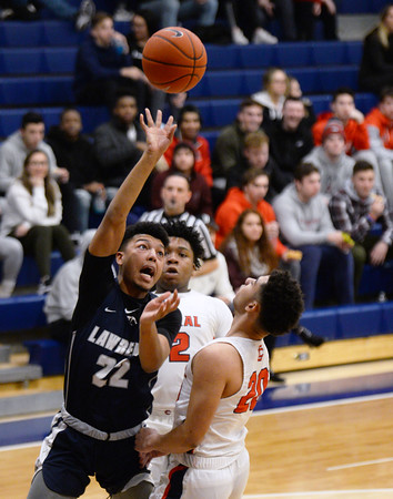 CARL RUSSO/Staff photo Lawrence's captain, Noah Tejada sails to the basket over Central's captain, Adrian Rodriguez. Central Catholic played against Lawrence in boys basketball action Tuesday night. 2/11/2020.