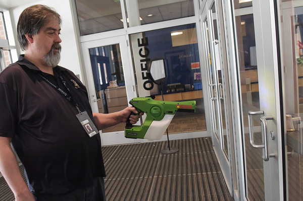 TIM JEAN/Staff photo <br /> <br /> Custodian Eric Russell, demonstrates how the germ blaster sprays a fine mist to disinfect surfaces on the door handles at the Hunking School in Haverhill.      2/14/20