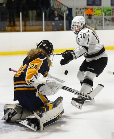 CARL RUSSO/Staff photo HPNA'S captain, Hannah Keating tries to control the puck after Andover's goalie, Lillian Jagger makes the save on her shot. HPNA (Haverhill, Pentucket, North Andover) defeated Andover 4-2 in girls' hockey action. 2/19/202.