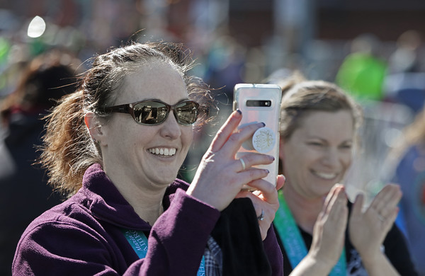 MIKE SPRINGER/Staff photo<br /> Abbie Takvorian of Chelmsford takes a photo of a friend at the finish line of the 13th annual Frozen Shamrock Road Race on Sunday in downtown Haverhill.<br /> 1/23/2020