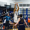 CARL RUSSO/Staff Photo. Andover's captain, Charlie McCarthy defends  against Lawrence's captain Brandon Goris as he takes the three point jump shot. Lawrence defeated Andover 60-54 in boys Basketball action in the D1 North tournament. 2/25/2020