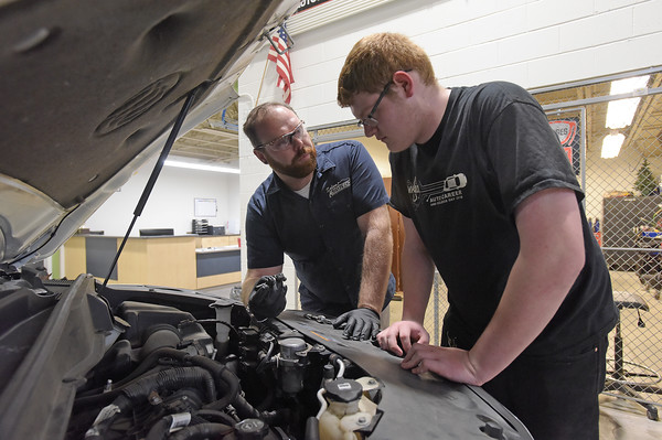 TIM JEAN/Staff photo <br /> <br /> High school senior Dylan Sykes, right, works along side of instructor Matt McCarthy, left, as they repair a problem on a vehicle in the Automotive Technology area of Salem high school's CTE center.     2/7/20