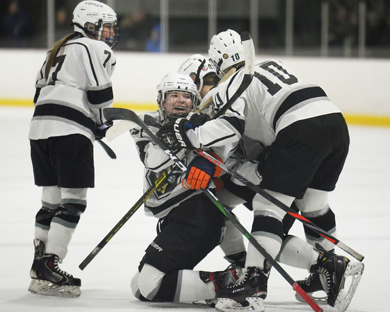 CARL RUSSO/Staff photo HPNA's captains, Eliana Kane is knocked down on the ice as she and her teammates, Morgan Whitlock, 7, Reese Pascucci, hidden and captain Hannah Keating, 10 celebrate the first goal of the game scored by Pascucci. HPNA (Haverhill, Pentucket, North Andover) defeated Andover 4-2 in girls' hockey action. 2/19/2020.