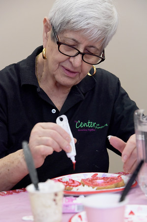 TIM JEAN/Staff photo <br /> <br /> Tina Solari, who volunteers in the kitchen, decorates a Valentine's Day cookie at the Andover Senior Center. The center is temporary in the basement of the Ballardvale Church on Clark Road. 2/12/20