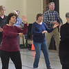 TIM JEAN/Staff photo <br /> <br /> <br /> Seniors are reflected in a mirror as they learn Tai Chi at Northern Essex Community College in Haverhill.    2/27/20