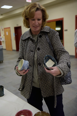 TIM JEAN/Staff photo <br /> <br /> Sally Goodwin, of Londonderry, tries to decide a bowl during the 15th annual Potter's Bowl fundraiser to benefit Community Caregivers of Greater Derry. The event was held at Pinkerton Academy in Derry, NH.     2/1/20