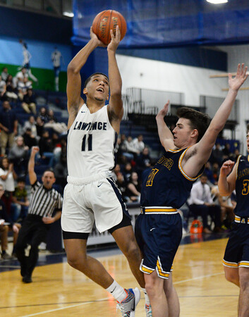 CARL RUSSO/Staff Photo. Andover's captain, Charlie McCarthy defends  against Lawrence's captain Brandon Goris as he drives to the hoop. Lawrence defeated Andover 60-54 in boys Basketball action in the D1 North tournament. 2/25/2020