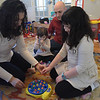 TIM JEAN/Staff photo <br /> <br /> Kyki Anastasiadis, 7, looks like she is playing a game, but is really part of her physical therapy to help improve her motor skills, and balance with her mother Panayiota. Kyki's father John Anastasiadis watches over them while playing a game with her younger sister Antigone, 2, as they play another game.   2/21/20