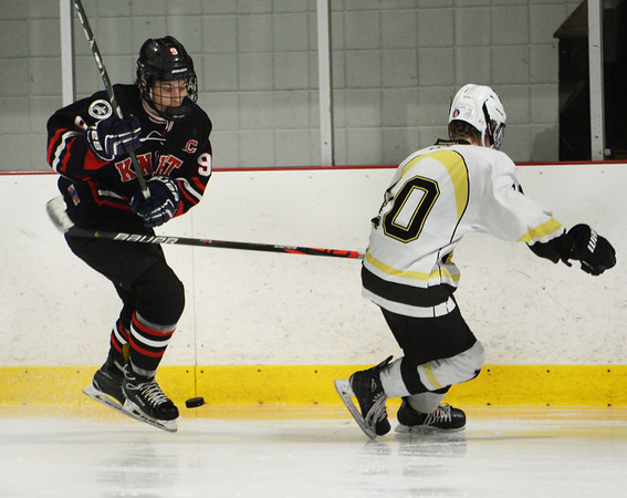 CARL RUSSO/Staff photo North Andover's T J Fredo maneuvers the puck around Haverhill's William Madden along the boards. North Andover defeated Haverhill 6-2 in boys' hockey action. 2/05/2020