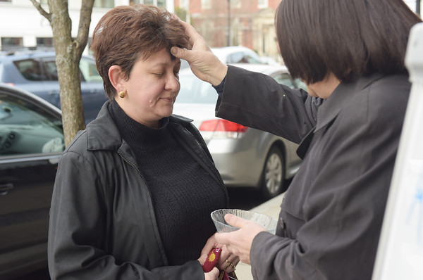 TIM JEAN/Staff photo <br /> <br /> Renee Manning, right, from South Church blesses Fabiana Murphy, of Andover, with ashes on Ash Wednesday outside of Starbucks in Andover. This year marked the fifth year South Church has given out ashes on the go in downtown Andover. 2/26/20