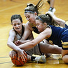 CARL RUSSO/Staff Photo Whittier's Linda Bullis, left fights for the loose ball with Winthrop players. Winthrop defeated Whittier Tech. 55-39 in Div. 3 North quarterfinals in girls basketball action Thursday night. 2/27/2020