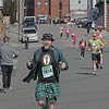 MIKE SPRINGER/Staff photo<br /> David Hanson of East Longmeadow holds a can of Guiness beer a miniature bottle of Jameson Irish whiskey as he approaches the finish line in the 13th annual Frozen Shamrock Road Race on Sunday in downtown Haverhill.<br /> 1/23/2020