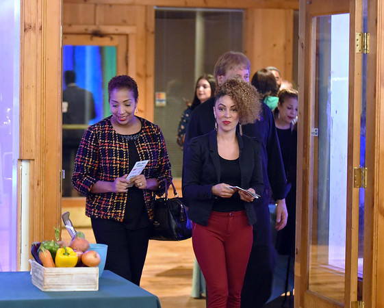 RYAN HUTTON/ Staff photo<br /> Esther Encarnacion, of the Lawrence Office of Planning and Development, left, and Loida Dominguez, right, enter the GLOW Gala at Everett Mill in Lawrence on Thursday night, November 14 marking the 20th anniversary of Groundwork Lawrence. 11/14/2019