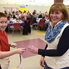TIM JEAN/Staff photo <br /> <br /> Volunteer Andrew Tanuma, 10, sells raffle tickets to MaryAnn Moser, of Derry, during the 15th annual Potter's Bowl fundraiser to benefit Community Caregivers of Greater Derry. The event was held at Pinkerton Academy in Derry, NH.     2/1/20