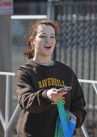 MIKE SPRINGER/Staff photo<br /> Ivy Ackerman, a junior with the Haverhill High School cross country team, hands out medals at the finish line of the 13th annual Frozen Shamrock Road Race on Sunday in downtown Haverhill.<br /> 1/23/2020