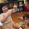 TIM JEAN/Staff photo <br /> <br /> Kyki Anastasiadis, 7, is all smiles as she looks like she is playing a game, but is really part of her physical therapy to help improve her motor skills, and balance. Her mother Panayiota, helps with the game while her younger sister Antigone, 2, sits on her lap.   2/21/20
