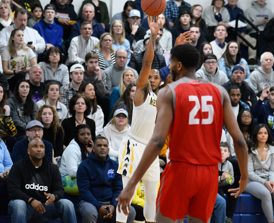 CARL RUSSO/Staff photo. Merrimack's Juvaris Hayes takes the three point jump shot in front of the sold out crowd. Merrimack College defeated Sacred Heart 64-57 in men's basketball action. 2/21/202.