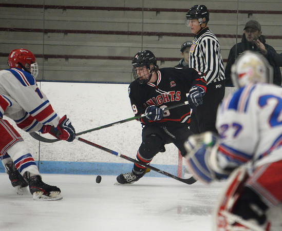 CARL RUSSO/Staff photo North Andover's T.J. Fredo fights for the puck near Tewksbury's goalie. <br /> <br /> North Andover defeated Tewksbury 3-2 in Div. 2 hockey quarterfinals at the Chelmsford Forum Friday night. 2/28/2020