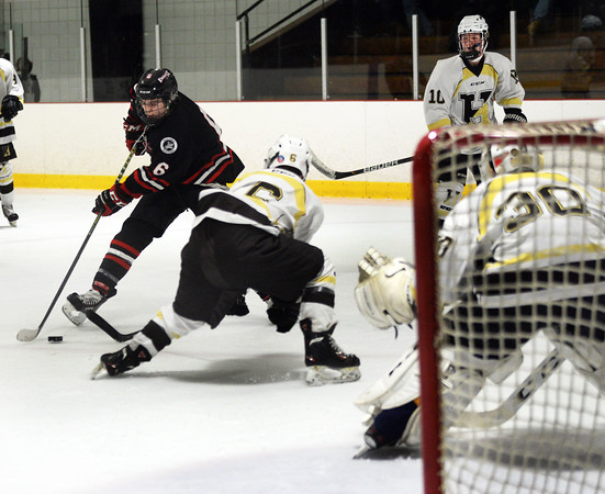 CARL RUSSO/Staff photo North Andover's Sean Corliss maneuvers around Haverhill's Jack Sullivan to take the backhand shot on Haverhill's goalie and captain Zach Roughan. North Andover defeated Haverhill in boys' hockey action. 2/05/2020