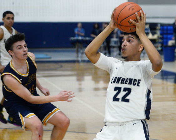 CARL RUSSO/Staff Photo. Lawrence's captain Noah Tejada gets the rebound before Andover's captain, Charlie McCarthy. Lawrence defeated Andover 60-54 in boys Basketball action in the D1 North tournament. 2/25/2020