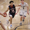 MIKE SPRINGER/Staff photo<br /> Central Catholic's Jonathan Peguero drives toward the basket against Jack Perry, right, of St. John's during varsity basketball action Sunday in Danvers. <br /> 2/2/2020