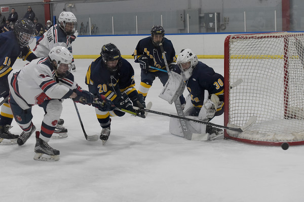 TIM JEAN/Staff photo <br /> <br /> Andover goaltender JJ Quill makes a save against Central's Robert DiBiasio, left, during a boys hockey game at the ICenter in Salem NH. Andover won 5-3.   2/8/20