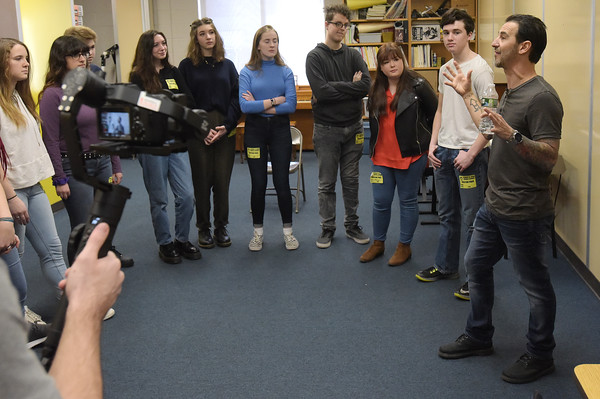 """TIM JEAN/Staff photo <br /> <br /> At right, Sully Erna, lead singer of rock band Godsmack talks Hood Middle School students as they learn part of a song before filming a video for  """"Unforgettable.""""      2/14/20"""