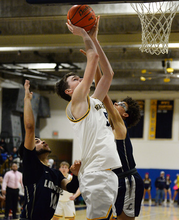 CARL RUSSO/Staff photo Andover's Aidan Cammann drives to the basket against Lawrence captain Angel Herrera, left and Jeremiah Melendez. Andover defeated Lawrence 66-57 in boys basketball action Friday night. 2/14/2020.
