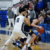 CARL RUSSO/Staff Photo. Andover's Ryan MacLellan comes up with the ball with Lawrence's captain, Angel Herrera on his back after a mad scramble for the loose ball. Lawrence defeated  Andover 60-54 in boys Basketball action in the D1 North tournament. 2/25/2020.