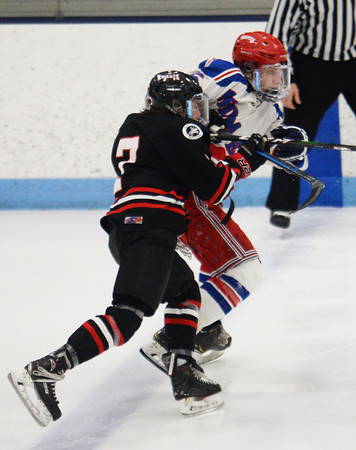 CARL RUSSO/Staff photo North Andover's Adam Heinze and Tewksbury's Tom Barbati fight for position as they chase the puck. <br /> <br /> North Andover defeated Tewksbury 3-2 in Div. 2 hockey quarterfinals at the Chelmsford Forum Friday night. 2/28/2020