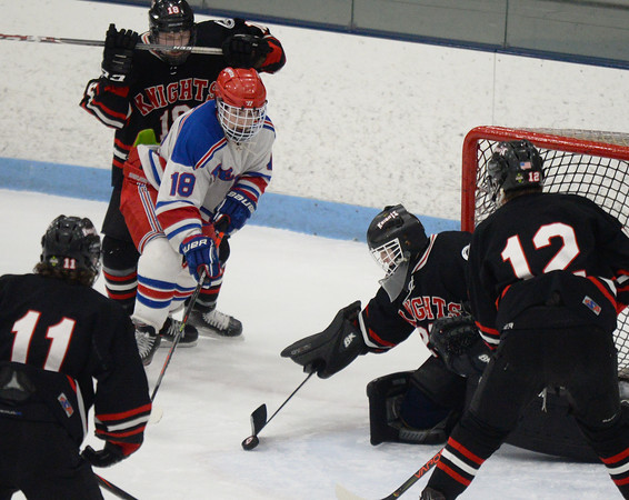 CARL RUSSO/Staff photo North Andover's goalie, Patrick Green makes the save as Tewksbury's Kyle Morris reaches for the puck. <br /> <br /> North Andover defeated Tewksbury 3-2 in Div. 2 hockey quarterfinals at the Chelmsford Forum Friday night. 2/28/2020