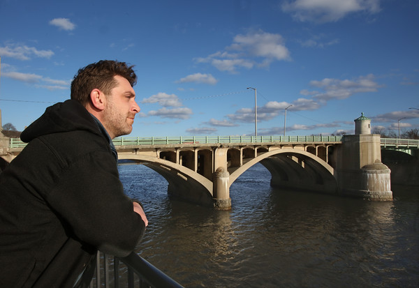 MIKE SPRINGER/Staff photo<br /> Poet Cody Kucker looks out over the Merrimack River in downtown Haverhill.<br /> 2/28/2020