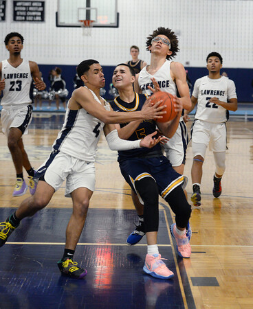 CARL RUSSO/Staff Photo. Andover's captain, Kyle Rocker struggles to make the lay up against Lawrence's Cristian Moscat, left and Jeremiah Melendez. Lawrence defeated  Andover 60-54 in boys Basketball action in the D1 North tournament. 2/25/2020