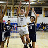 CARL RUSSO/Staff photo Andover captain Charlie McCarthy sails to the hoop against Lawrence captain Brandon Goris, left and Jeremiah Melendez. Andover defeated Lawrence 66-57 in boys basketball action Friday night. 2/14/2020.