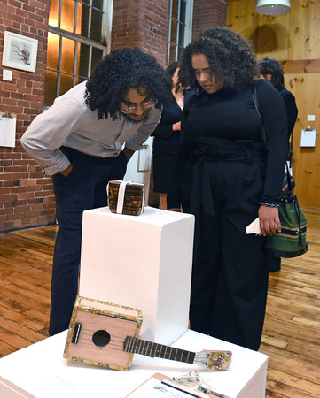 RYAN HUTTON/ Staff photo<br /> Mekhi Mendoza, left, and Celeste Cruz, right, check out some of the art work on display at the GLOW Gala at Everett Mill in Lawrence on Thursday night, <br /> November 14 marking the 20th anniversary of Groundwork Lawrence. 11/14/2019