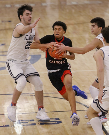 MIKE SPRINGER/Staff photo<br /> Xavier McKenzie of Central Catholic drives the ball through a group of St. John's defenders during varsity basketball action Sunday in Danvers. <br /> 2/2/2020
