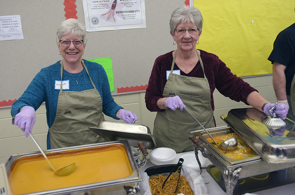 TIM JEAN/Staff photo <br /> <br /> Volunteers Marybeth Zinni, left, and Eileen Hegarty, both of Londonderry, stirs up the soup during the 15th annual Potter's Bowl fundraiser to benefit Community Caregivers of Greater Derry. The event was held at Pinkerton Academy in Derry, NH.     2/1/20