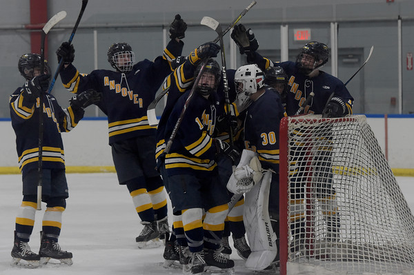 TIM JEAN/Staff photo <br /> <br /> Andover goalie JJ Quill (30) is swarmed by his teammates after defeating Central 5-3 at the ICenter in Salem NH.     2/8/20