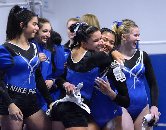 CARL RUSSO/Staff photo Methuen junior, Molly Beeley  hugs senior captain, Adiamis Ramos as the Rangers congratulate Ramos after her performance on the bars at the Merrimack Valley Conference Gymnastic League Meet on February 6, at A2 Gym and Cheer in Salem NH. <br /> <br /> The Rangers had more reasons to celebrate after they captured the MVC Division 2 championship. Ramos also captured the Senior Gymnast of The Year title.  2/6/2020